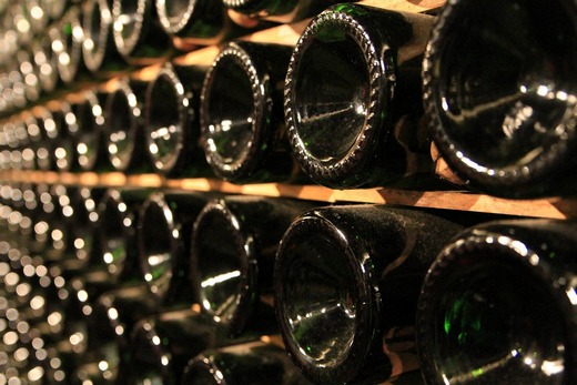 A close up of rows or bottles in a wine cellar.