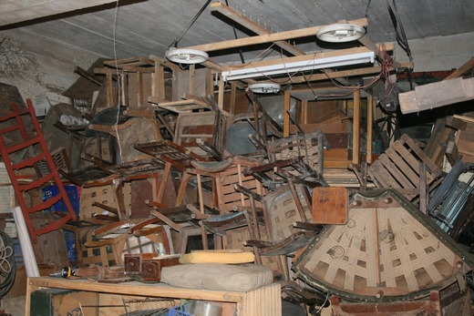 A cluttered basement full of old furniture
