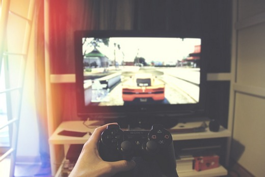Sitting in front of a TV playing a game with racing cars.