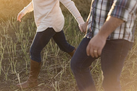Man and a woman holding hands while walking through a field.