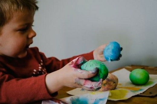A boy playing with colours and material shapes