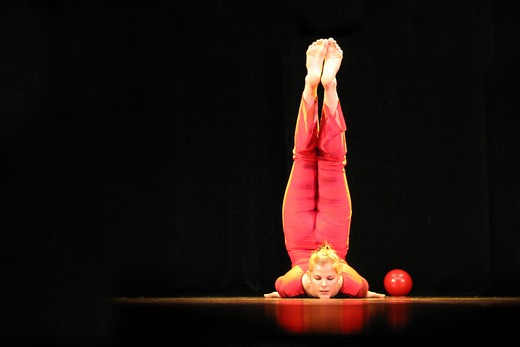A woman gymnast doing a leg stand