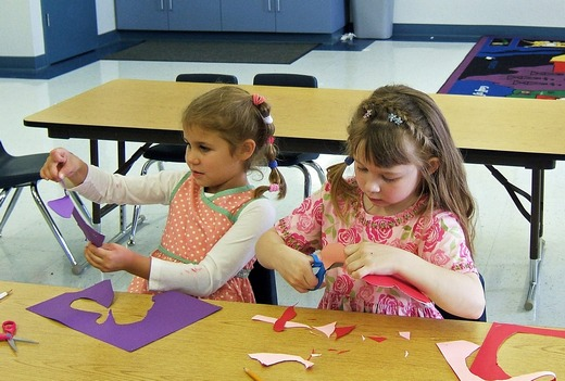 Two little girls making paper cutouts