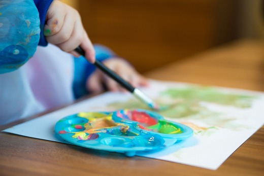 A toddler playing with colours on paper