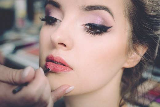 Makeup artist at work on woman's lips