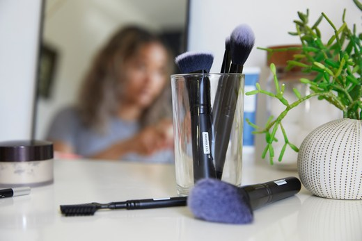 Makeup brushes on a table, with makeup artist blurred in background