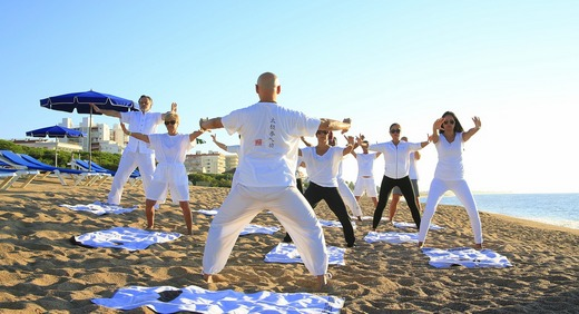 A group of people doing yoga exercises on beach