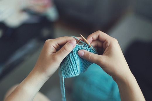 Two hands knitting in blue